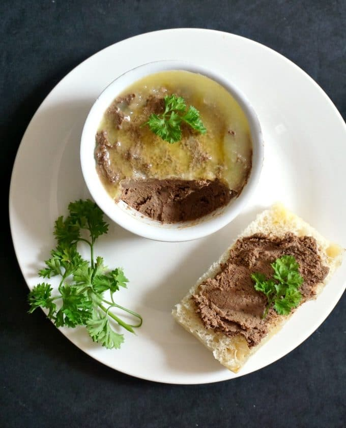 Overhead view of a white plate with a rameskin of chicken liver pate, and a slice of bread spread with pate