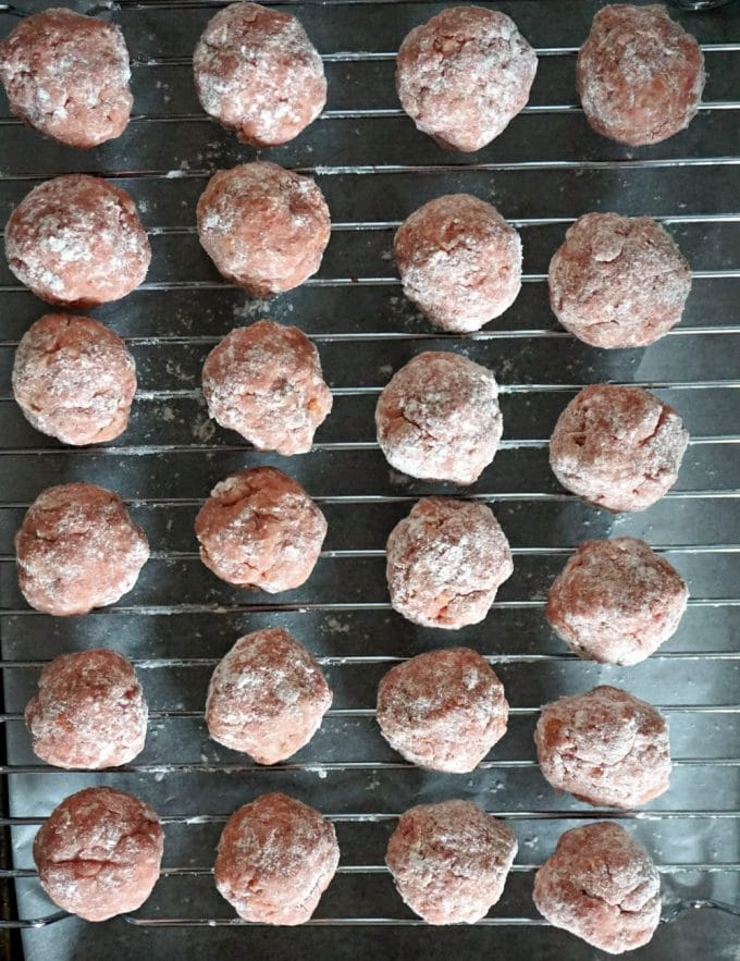 24 raw Swedish meatballs on an oven rack ready to be baked