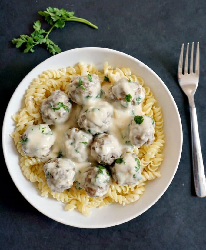 Overhead shot of a white plate of pasta and swedish meatballs with a fork next to the plate on the right hand side and a parsley spring at the top