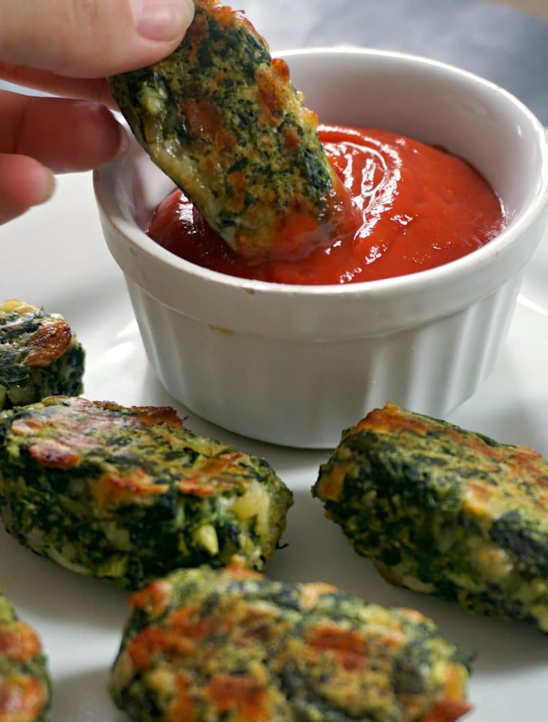 A Brussels Sprout Spinach bite dipped into a rameskin of ketchup, with other bites next to it