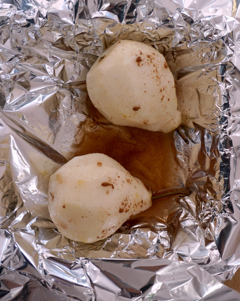 Overhead shot of 2 oven-poached pear ghosts on a kitchen foil