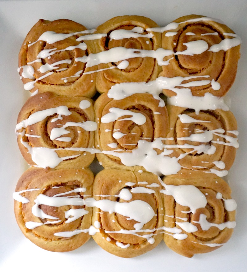 9 pumpkin pie cinnamon rolls on a white plate