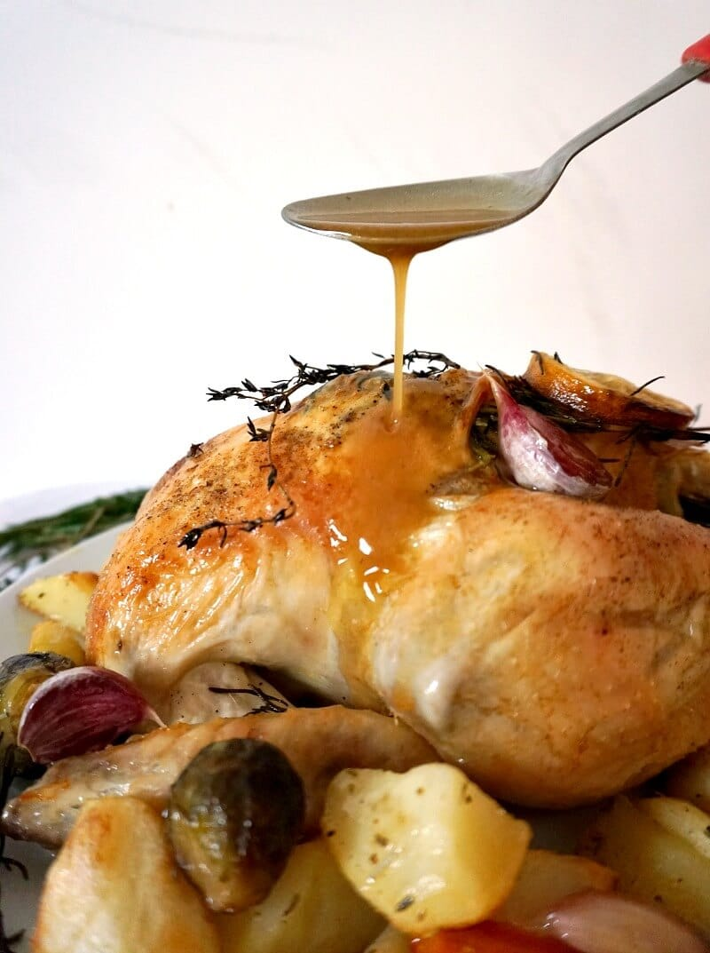 Gravy pouring from a spoon over a plate of roasted chicken and vegetables