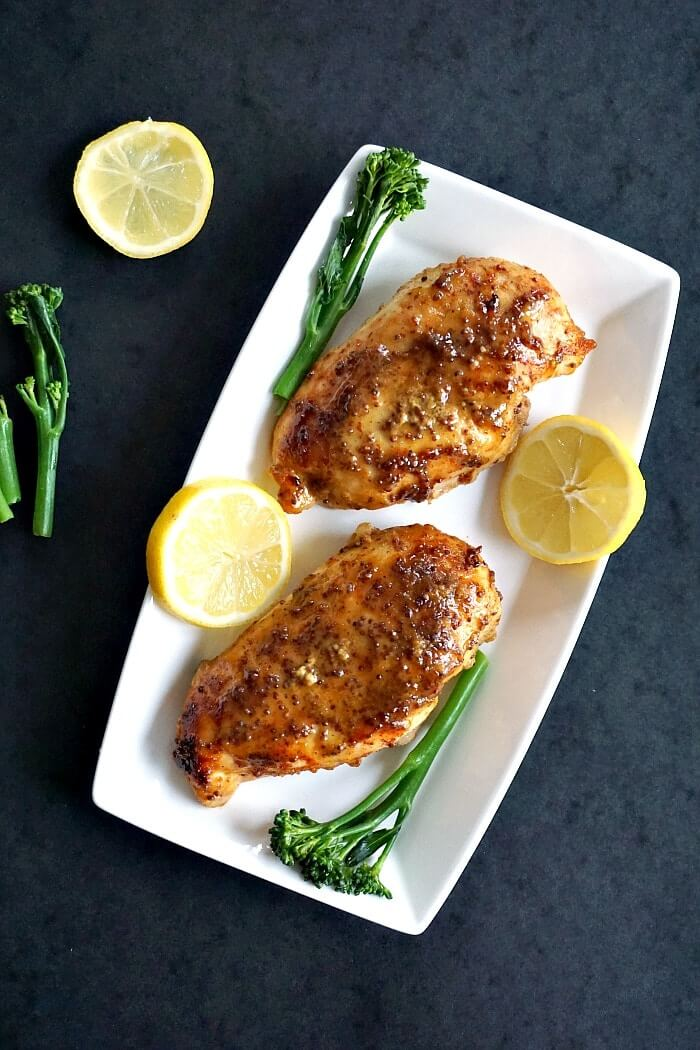 Overhead shoot of a white rectangle plate with 2 chicken breasts flanked by 2 slices of lemon and broccoli spears