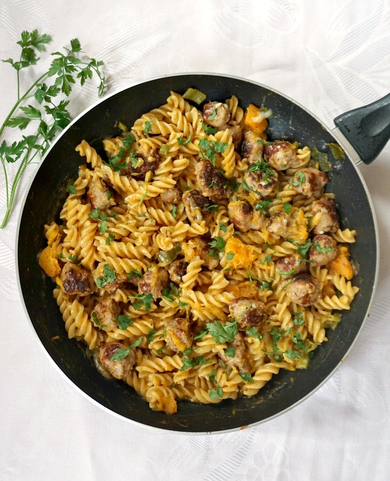 Overhead shot of a black pan with butternut squash sausage pasta on a white table cloth with a parsley sprig next to it