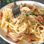 A white plate of bacon carbonara pasta