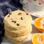 A stack of 4 Cranberry Orange Cookies with 2 halves of an orange, and a cup of coffee