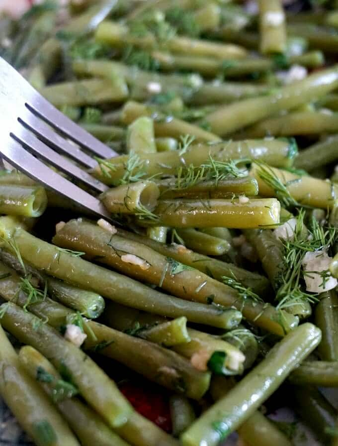 A fork digging into some sauteed green beans