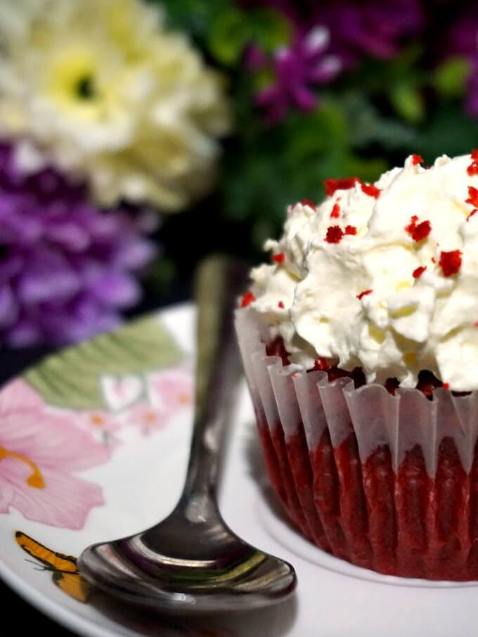 Half a red velvet cupcake on a small plate with a dessert spoon next to it
