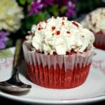 A red velvet cupcake on a small plate with a dessert spoon next to it and coloured flowers in the background