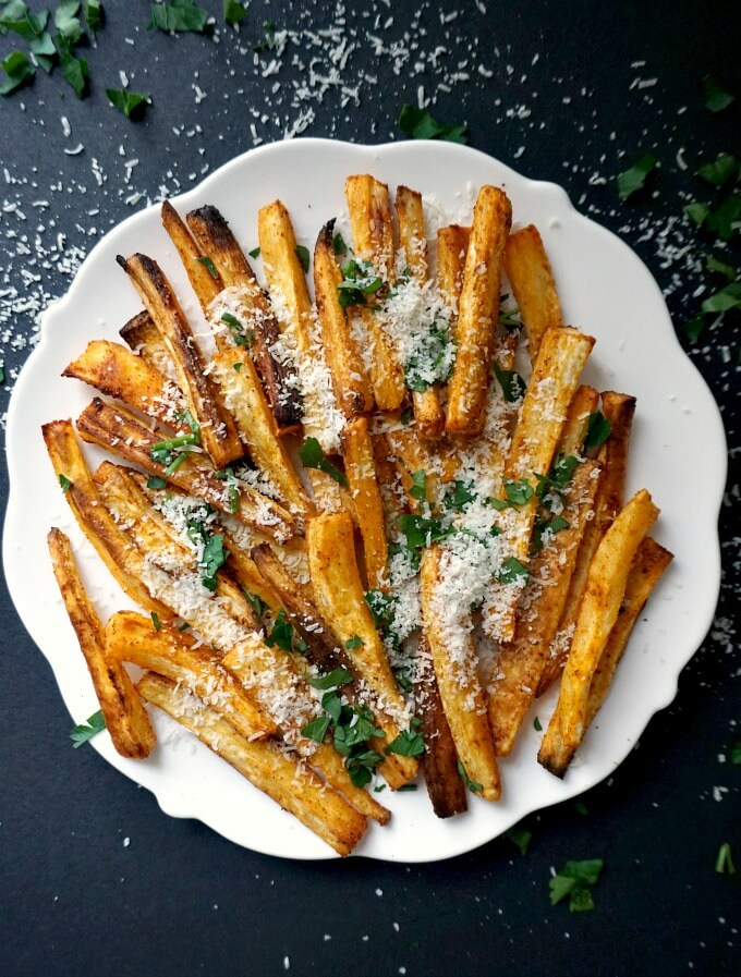 Overhead shot of a white plate with baked parsnip fries topped with grated parmesan and chopped parsley