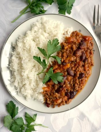 Overhead shot of a white plate with rice and homemade chili with rice and a sprig of fresh parsley on top