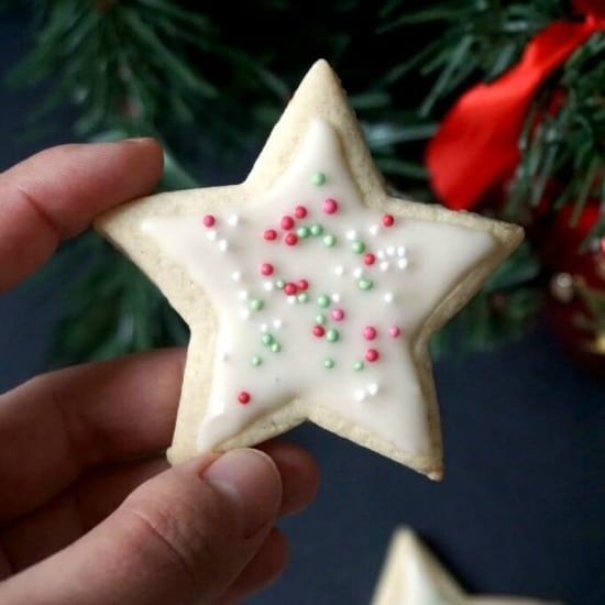 Hand holding a Christmas Iced Cookie over a Christmas tree background