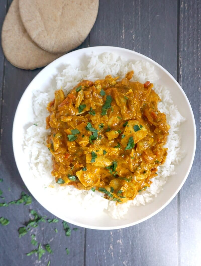 Overhead shoot of a white plate with rice and chicken curry