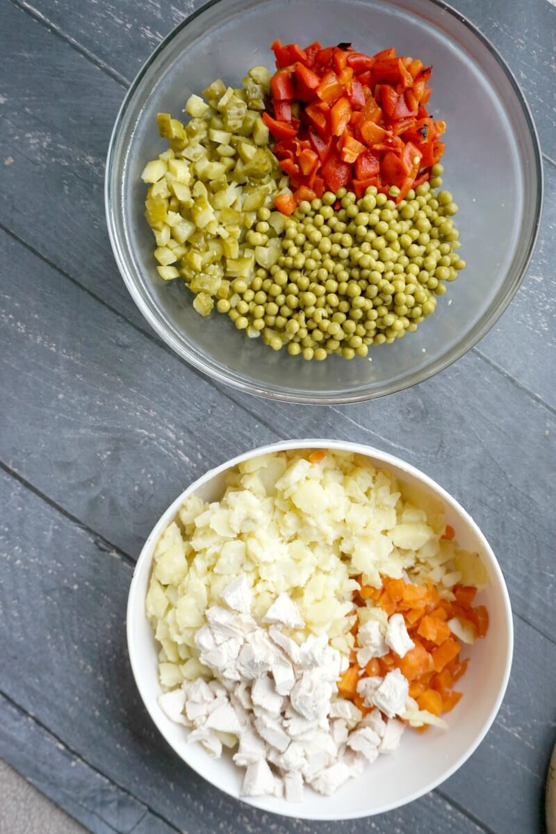 Overehead shoot of a bowl with chopped gherkins, pickled red peppers and peas, and another bowl with chopped boiled potatoes, carrots and chicken