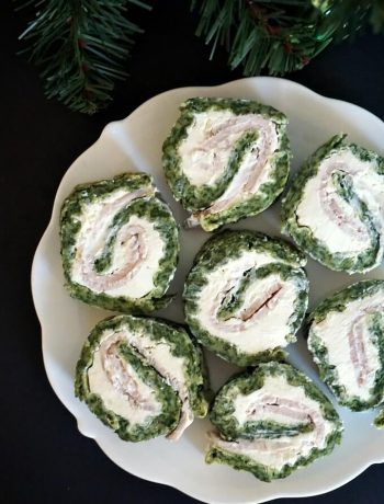 7 spinach roll ups with ham and cream cheese on a white plate