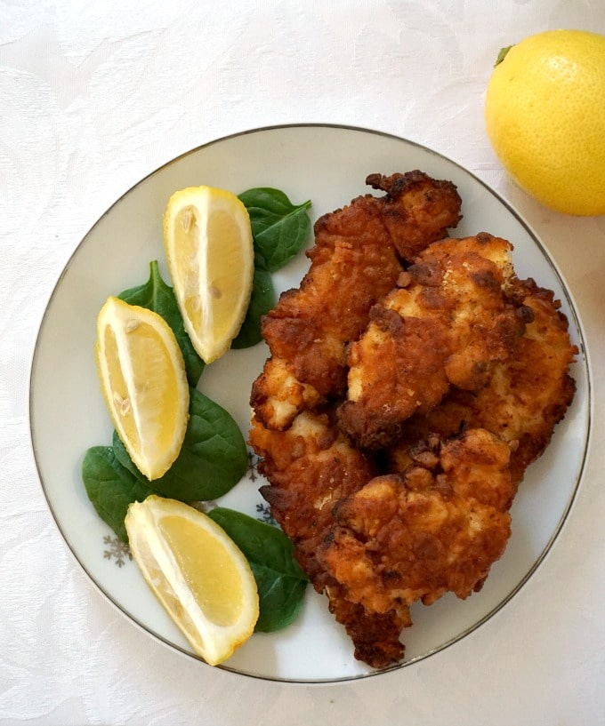 Overhead shot of a white plate with fired butermilk chicken tenders and 3 lemon wedges on some spinach leaves