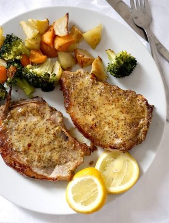 Baked honey mustard pork chops with broccoli and roast carrots and potatoes and 2 lemon slices on a white plate
