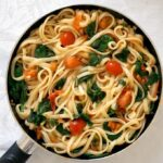 Overhead shot of a pan with pasta with spinach and tomatoes