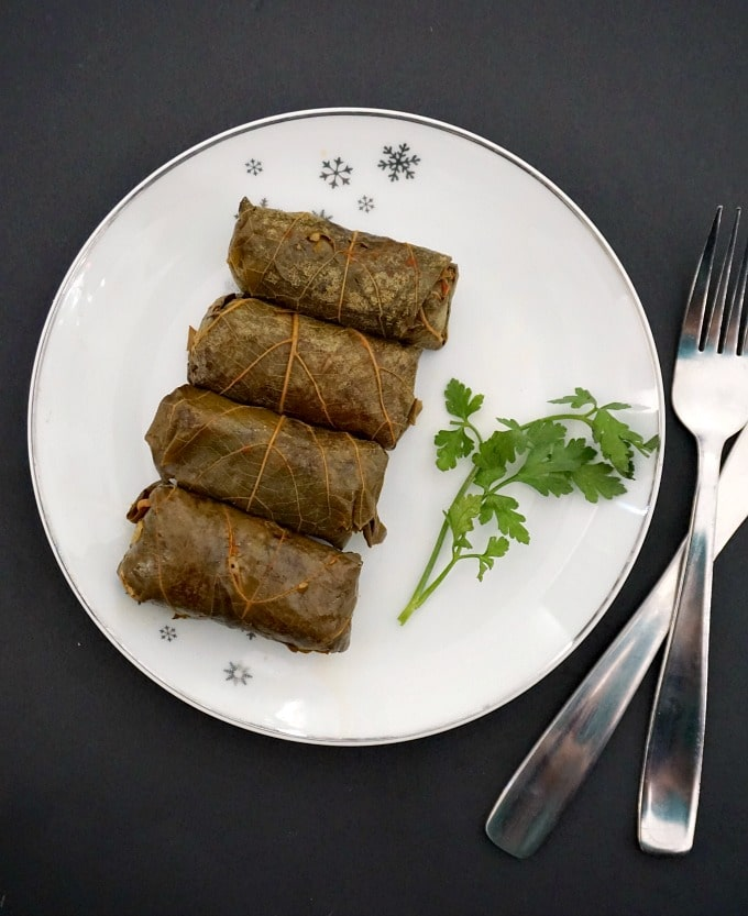 Overhead shot of a white plate with 4 vegetarian stuffed grape leaves and some parsley leaves, plus a fork and a knife next to the plate