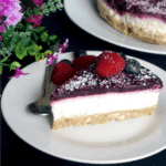 A slice of coconut cheesecake on a white plate with a teaspoon next to it, another white plate with cheesecake and flowers in the background