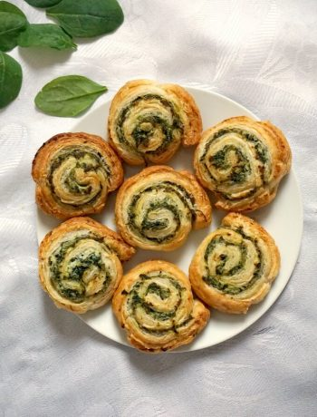Overhead shot of a white plate with 7 spinach pinwheels and some spinach leaves around the plate