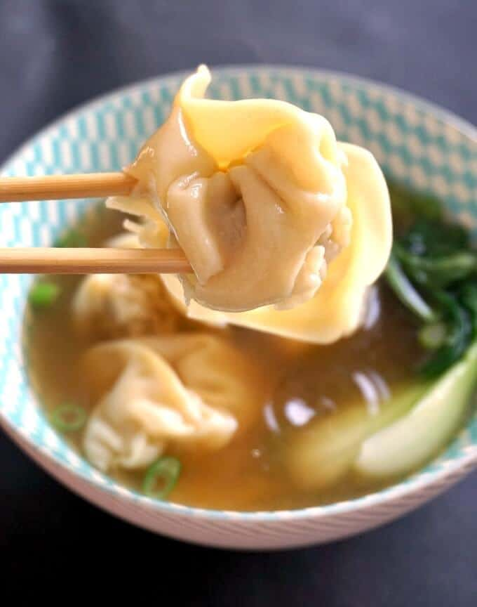A wonton dumpling picked by chocpsticks, with a bowl of wonton soup in the background