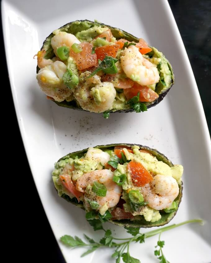 Oveerhead shot of a white plate with 2 avocado skins stuffed with avocado shrimp salad