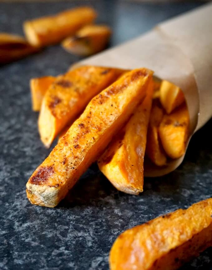Crispy baked sweet potato fries scattered on a black table