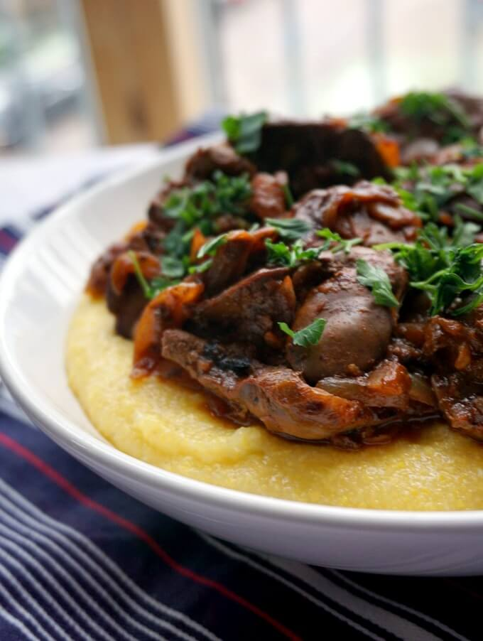 Close-up shot of a plate of chicken liver and onions over polenta