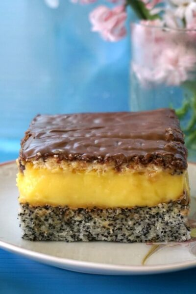 A slice of poppy seed cake with homemade vanilla custard and nutella on a small plate with a glass of flowers in the background