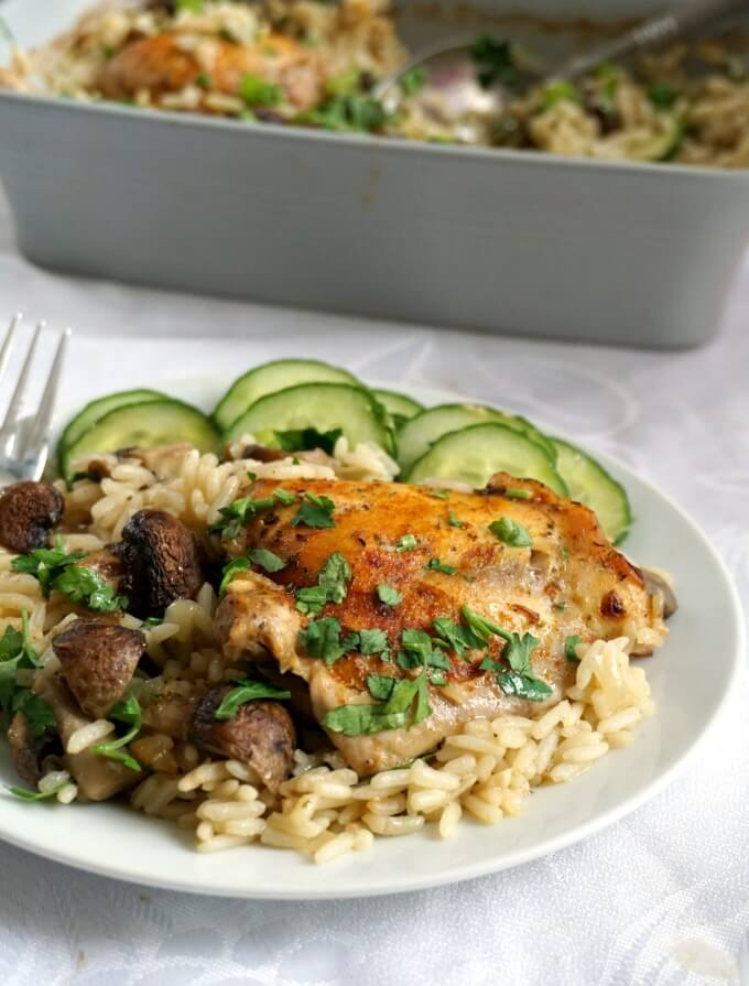 A white plate with baked chicken with rice and mushrooms and a cucumber salad on the side. Another pan with baked chicken with rice and mushrooms in the background