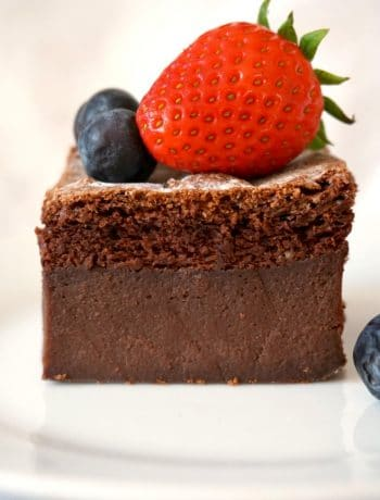 A slice of chocolate magic cake topped with a strawberry and 3 blueberries