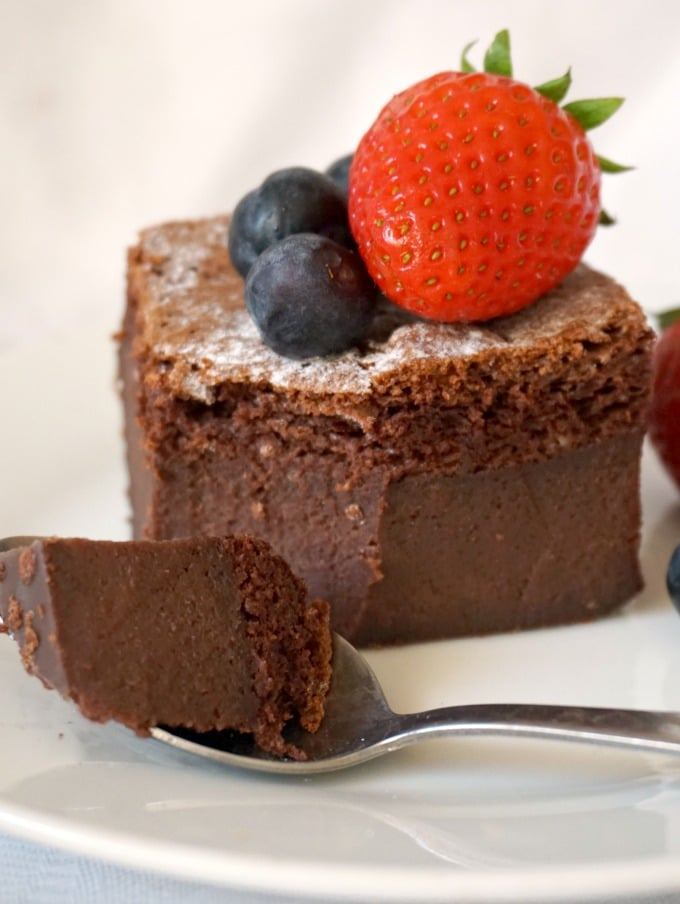 A slice of chocolate magic cake with a dessert spoon next to it