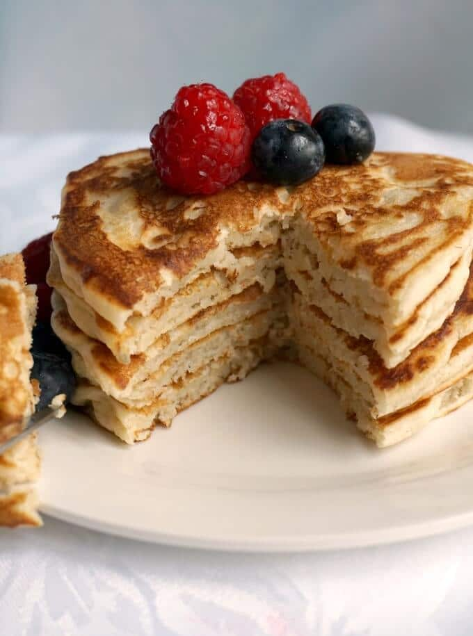 A stack of egg-free pancakes on a white plate topped with berries