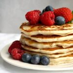A stack of 6 egg-free pancakes topped with berries