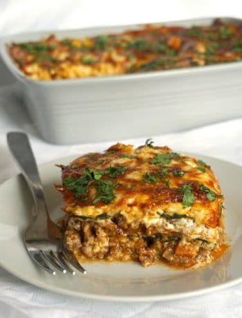 A white plate with a slice of high protein low carb zucchini lasagna and a dish of lasagna in the background