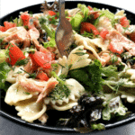 A black bowl of pasta salad with salmon, tomatoes and salad leaves