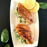 Overehead shot of a white rectangle plate with 2 spinach-stuffed chicken breasts, and 2 lemon slices next to them