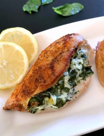 A baked spinach-stuffed chicken breast on a white plate with 2 lemon slices next to it