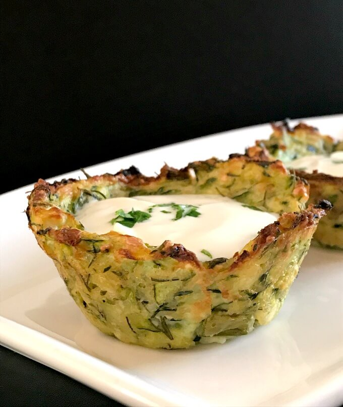 One baked zucchini bite on a white plate