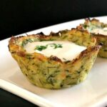 A baked zucchini bite on a white plate