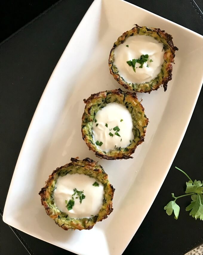 Overhead shot of a white plate with 3 baked zucchini bites in it