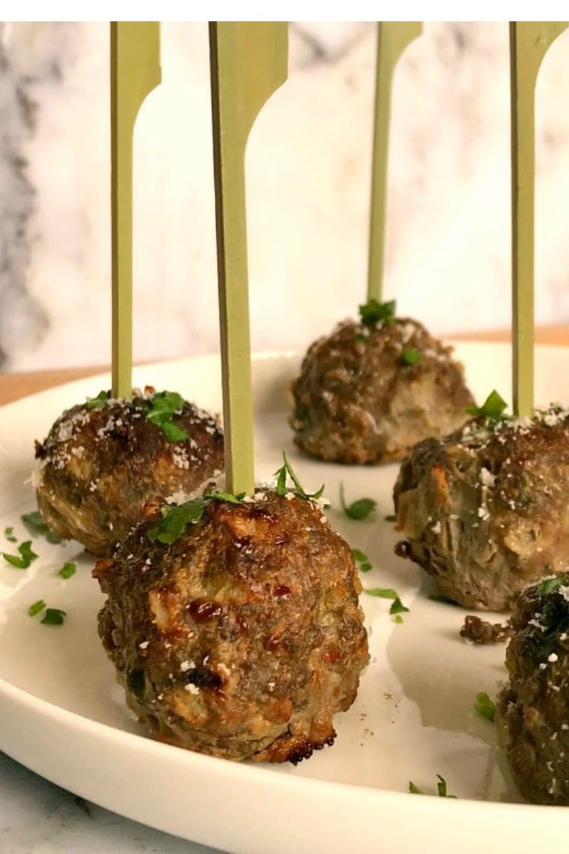5 baked italian meatballs on a white plate with serving sticks on them