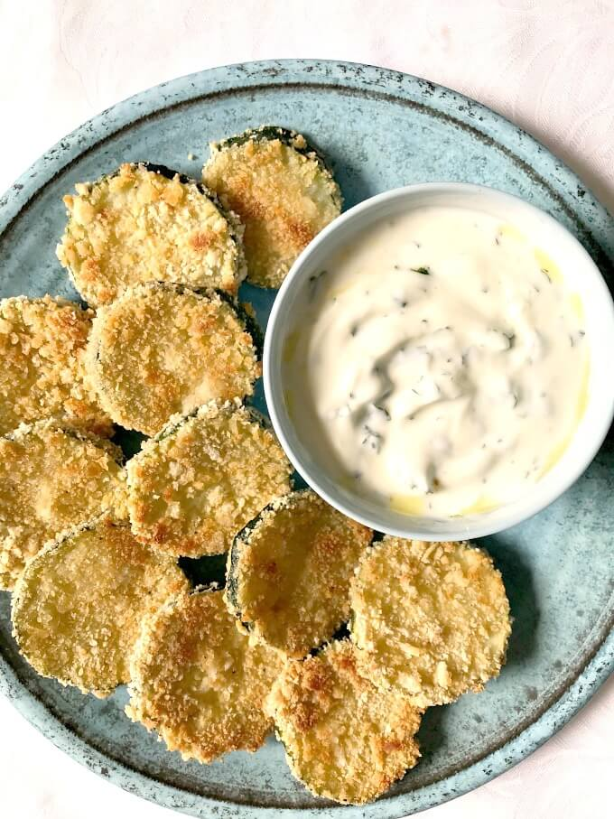 Overhead shoot of a blue plate with a bowl of yogurt garlic sauce and baked zucchini chips