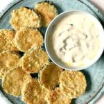 Overhead shoot of a blue plate with baked zucchini chips and a small bowl of yogurt garlic sauce