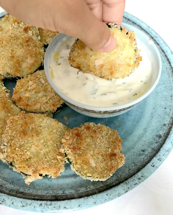 A baked Zucchini chip being dipped in a bowl of yogurt garlic sauce with other chips around the bowl