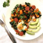 Overhead shoot of a white plate with breakfast sweet potato hash, 4 slices of avocado next to it, and fork and knife on the side of the plate