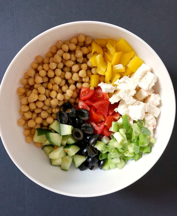 A white bowl of Chickpeas sliced tomatoes, yellow pepper, feta, sliced black olives, spring onions and cucumbers to make Mediterranean Chickpea Salad with Feta