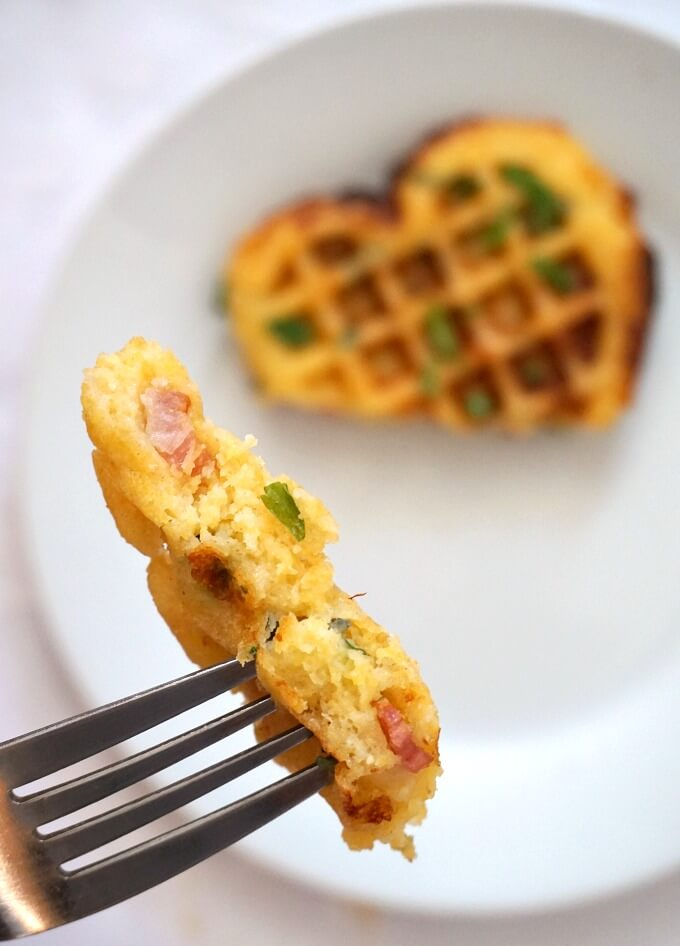 A fork showing a piece of cornbread waffle with a white plate and a waffle in the background